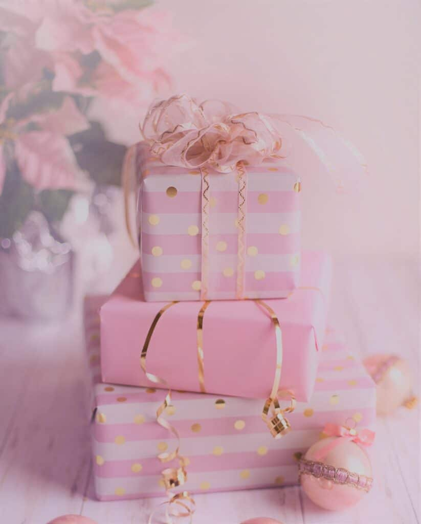 how to volunteer and be an elf all year - stack of pink gifts