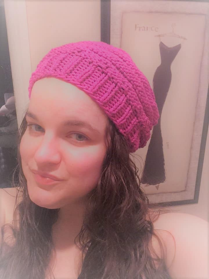 knitting hats for charity; Michele Kelsey with knitted hat